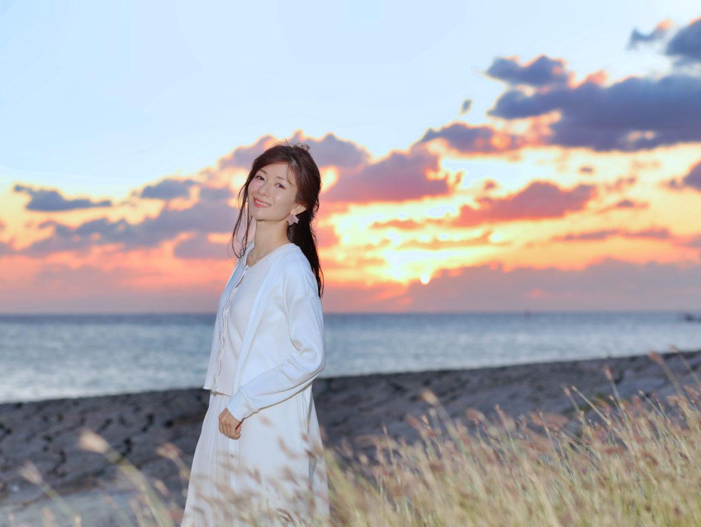 大城優紀が夕暮れのちゅらさんビーチの中、笑っているポートレート写真