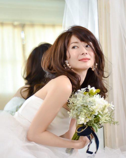 沖縄のシンデレラデコレーションでドレスを着て撮影した大城優紀の写真。手に花束を持って座っている。