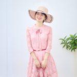 大城優紀が白壁の前でピンクのワンピースに帽子をかぶって立っている写真。カメラマンのプランディが撮影。