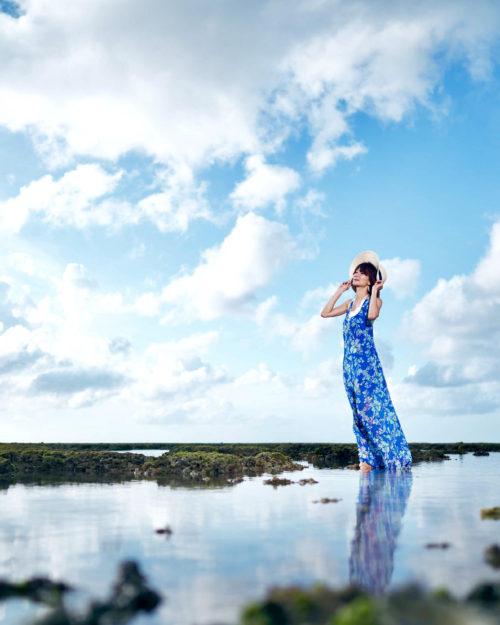 沖縄の海で撮影した夏のポートレート写真。大城優紀が海と夏空を背景に、青いワンピーズを着て立っている全身写真
