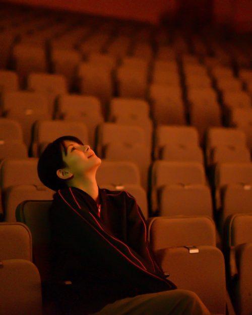 てぃるるのホールの客席に座って上を見ている舞台本番前の大城優紀の写真。